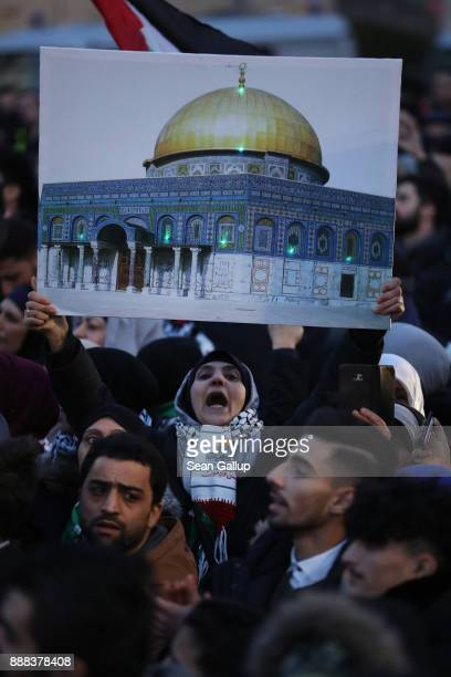 A woman holds up a photograph of the AlAqsa mosque in Jerusalem among people among people who had gathered in front of the US Embassy and the...