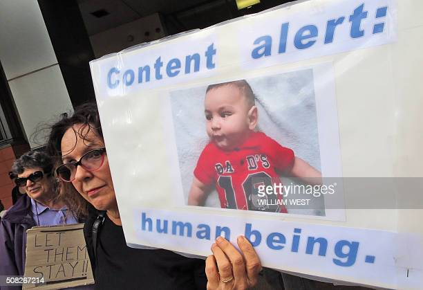 A woman holds up a placard at a protest outside an immigration office in Sydney on February 4 as Australian church leaders said they would offer...
