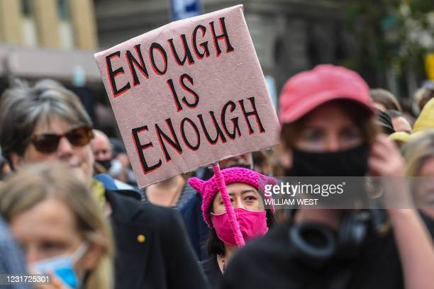 Woman holds up a placard during a protest against sexual violence and gender inequality in Melbourne on March 15, 2021. / The erroneous mention[s]...
