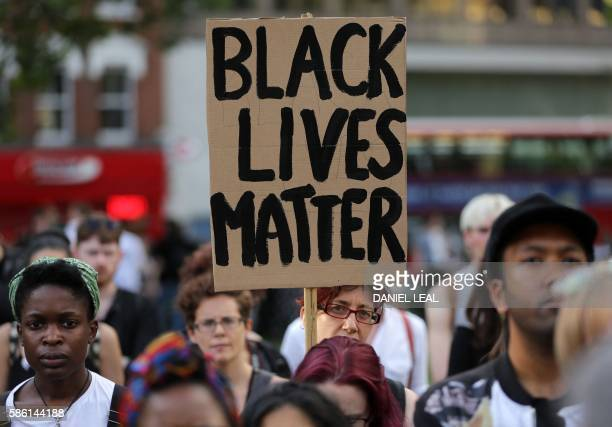 A woman holds up a placard in Altab Ali Park in east London as she attends a Black Lives Matter event on August 5 2016 The group inspired by the US...