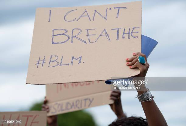 A woman holds up a placard reading I can't breathe as she protests against racism and pays tribute to George Floyd during a Black Lives Matter...