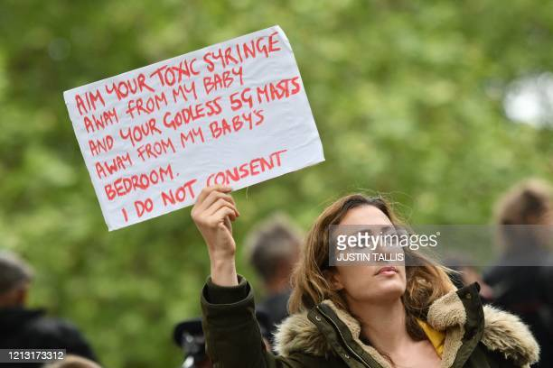 Woman holds up a placard with anti-vaccination and anti-5G messages at an anti-coronavirus lockdown demonstration in Hyde Park in London on May 16...