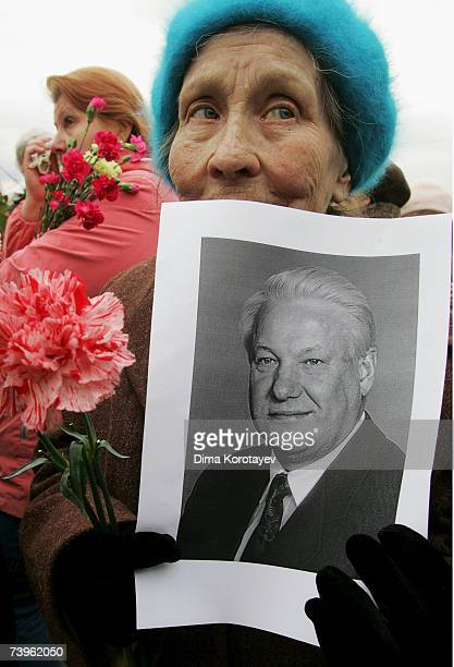 A woman holds up a portrait and a rose as people queue to view the body of former Russian President Boris Yeltsin as he lies in state in the Christ...