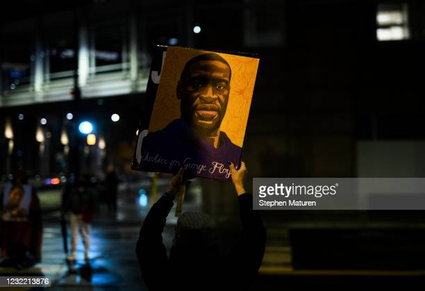 Woman holds up a portrait of George Floyd as people gather outside the Hennepin County Government Center on April 9, 2021 in Minneapolis, Minnesota....