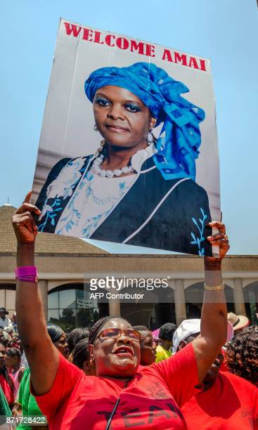 A woman holds up a portrait of Grace Mugabe during a gathering of President's supporters at his party headquarters to show support to Grace Mugabe...