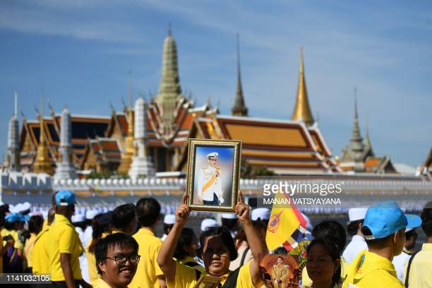 Woman holds up a portrait of Thailand's King Maha Vajiralongkorn in front of the Grand Palace ahead of his coronation in Bangkok on May 4, 2019.