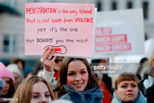 Woman holds up a poster as she takes part in a Women's March in front of the Brandenburg Gate on January 19, 2019 in Berlin. - The Women's March...