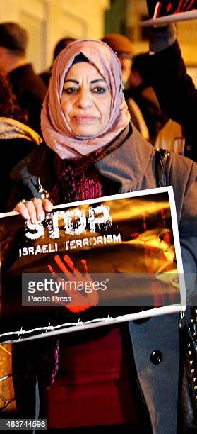 A woman holds up a poster during a vigil for the victims of the latest ISIS terror killings in the West Bank city of Beit Sahur Following another...