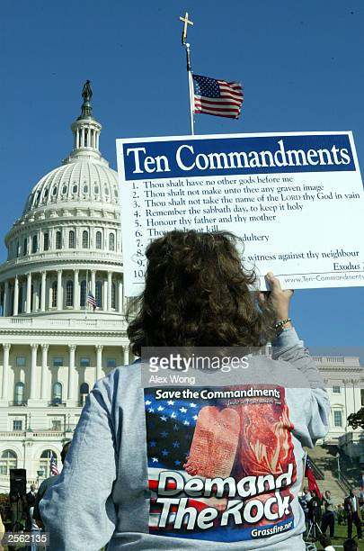 A woman holds up a poster of the Ten Commandments October 5 2003 during a rally at the West Lawn of the US Capitol in Washington DC Christian...