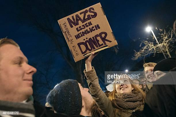 A woman holds up a poster reading Nazis clandestinely eat doner kebab in protest against a rally by a mounting rightwing populist movement on January...