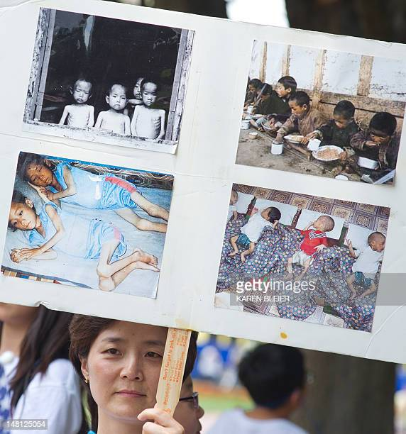 A woman holds up a poster with photos from an internment camp in North Korea during a White House vigil at Lafayette Park July 10 2012 In Washington...