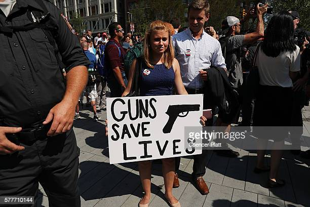 A woman holds up a pro gun sign near the site of the Republican National Convention in downtown Cleveland on the second day of the convention on July...