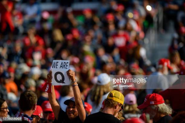 Woman holds up a QAnon sign to the media as attendees wait for President Donald Trump to speak at a campaign rally at Atlantic Aviation on September...