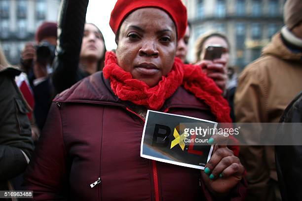 A woman holds up a sign as a mark of solidarity as people leave tributes at the Place de la Bourse following today's attacks on March 22 2016 in...