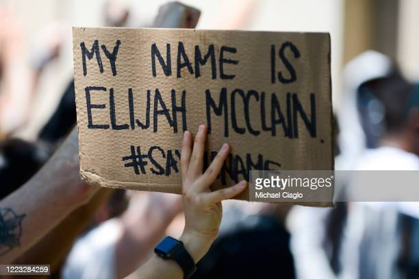 A woman holds up a sign as people rally outside the Aurora Police Department Headquarters to demand justice for Elijah McClain on June 27 2020 in...