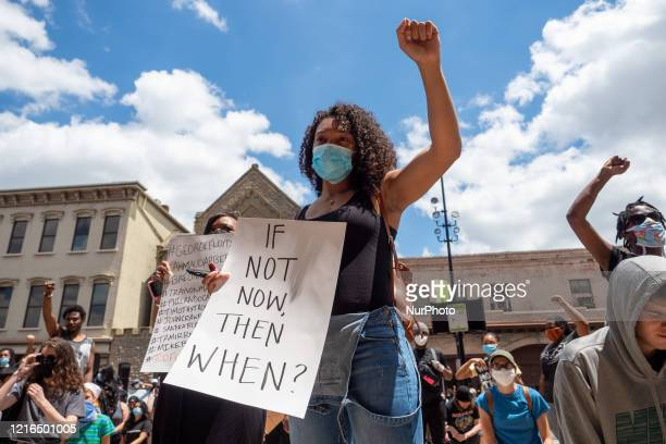 A woman holds up a sign during a Mass Action for Black Liberation protest and march from Washington Park to City Hall following the alleged murder of...