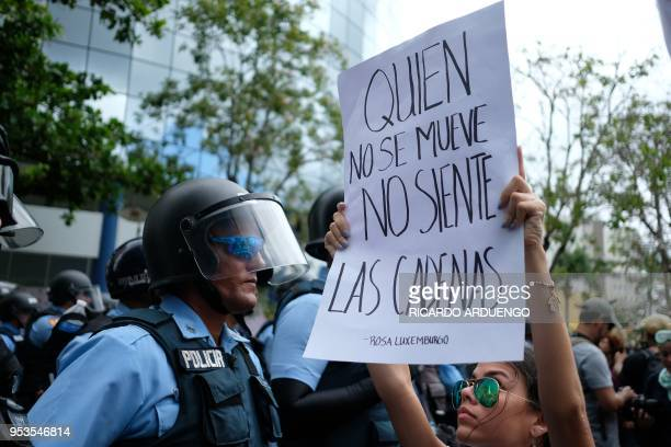 A woman holds up a sign in front of a riot police line during a May Day protest against pension cuts school closures and slow hurricane recovery...