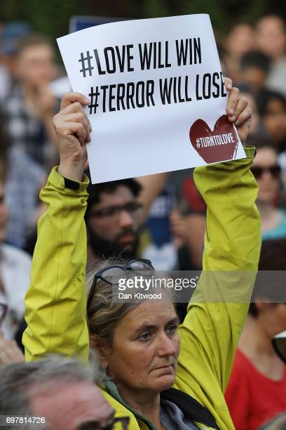 A woman holds up a sign saying 'love will win terror will lose' as she attends a vigil outside Finsbury Park Mosque on June 19 2017 in London England...