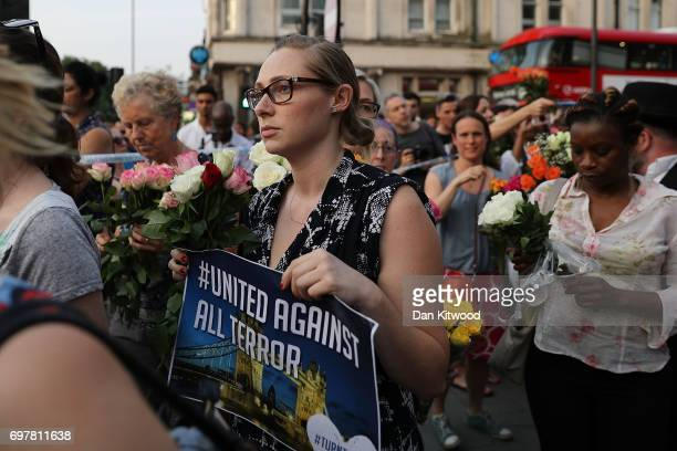 A woman holds up a sign saying 'united against terror' as she attends a vigil outside Finsbury Park Mosque on June 19 2017 in London England...