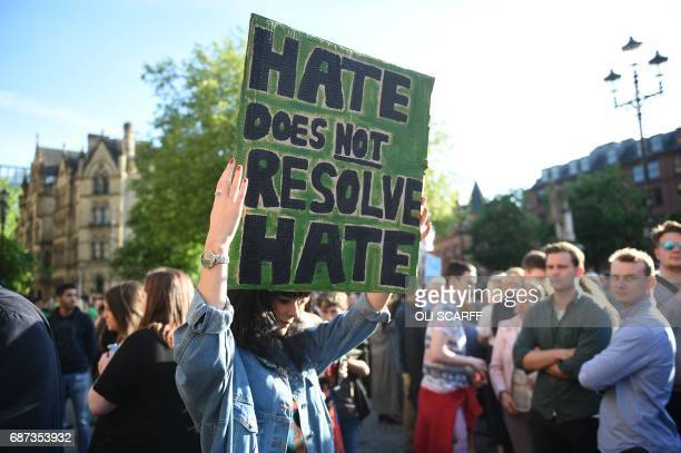 A woman holds up a sign that reads 'Hate Does Not Resolve Hate' during a vigil in Albert Square in Manchester northwest England on May 23 in...