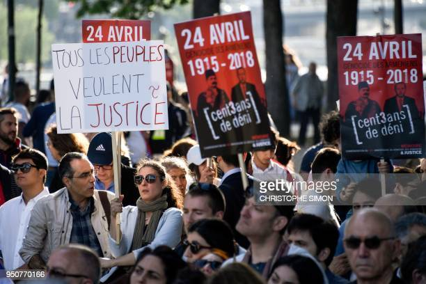 A woman holds up a sign that reads in French 'All people want justice' as Armenians gather to commemorate the 103rd anniversary of the Armenian...