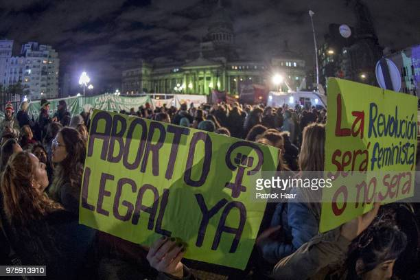 A woman holds up a sign that reads 'Legal abortion now The revolution will be feminist or it will not be' during a rally to demand legal and free...