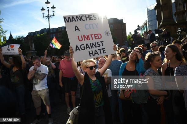 A woman holds up a sign that reads 'Manchester A City United Against Hate' during a vigil in Albert Square in Manchester northwest England on May 23...
