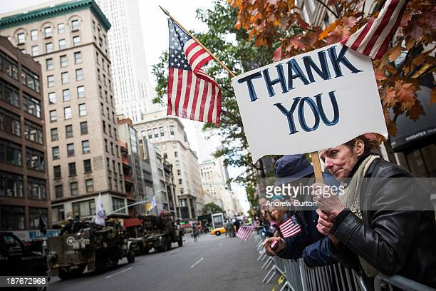 A woman holds up a sign that says Thank You during the Veteran's Day Parade on November 11 2013 in New York City The parade included members of all...