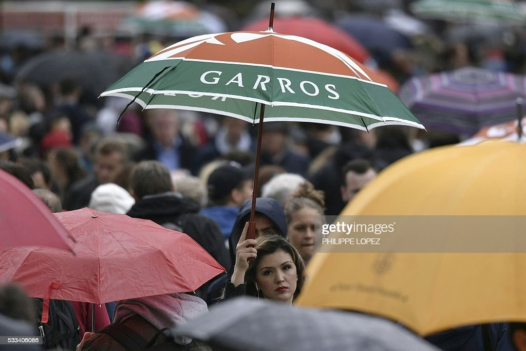 TOPSHOT - A woman holds up an umbrella after play was interrupted due to rain at the Roland Garros 2016 French Tennis Open in Paris on May 22, 2016. / AFP / Philippe LOPEZ