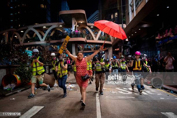 Woman holds up an umbrella and license plates, one that reads 'love', during violent protests between riot police and demonstrators in the Causeway...