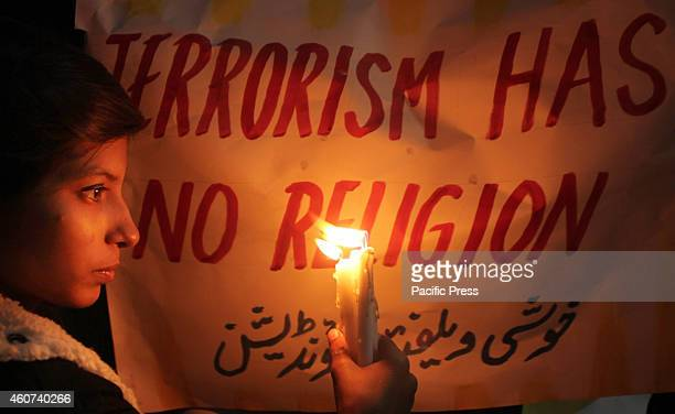 A woman holds up candles to pay tribute to the victims killed in Tuesday's Taliban attack on a militaryrun school in Peshawar in Lahore At least 148...