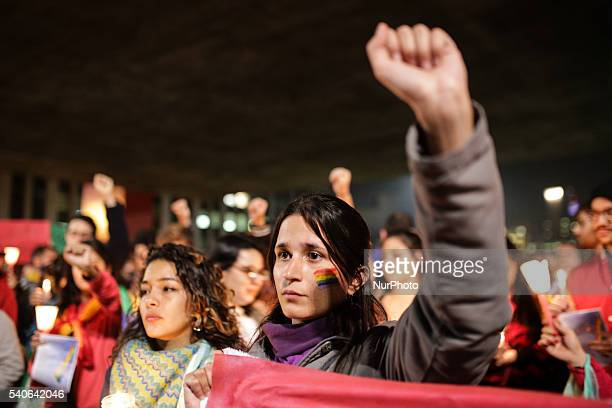 A woman holds up her fist during a vigil in memory of victims of the mass shooting at the Pulse gay night club in Orlando in Sao Paulo Brazil on June...