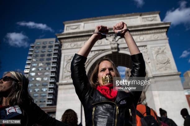 A woman holds up her handcuffed arms as she attends a rally to mark International Women's Day in Washington Square Park March 8 2017 in New York City...