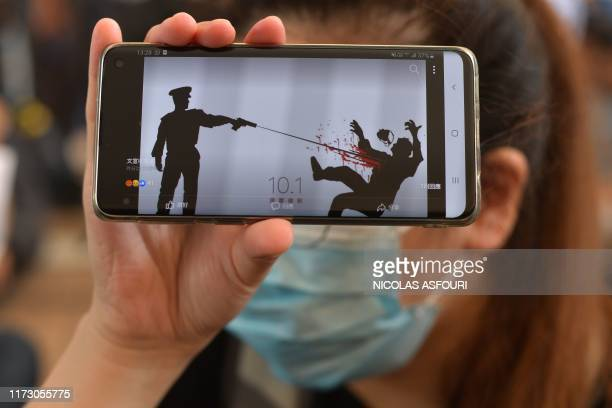 TOPSHOT A woman holds up her phone showing a image as protesters and supporters gather outside the entrance to the West Kowloon Court in Hong Kong on...