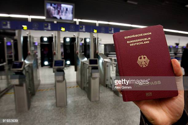 A woman holds up passport during the presentation of the new automated border control system easyPass at Frankfurt International Airport on October...