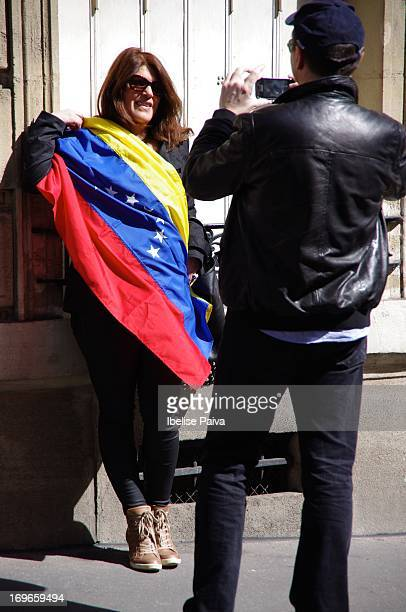 Woman holds Venezuela's flag while man takes her picture during the presidential elections of Venezuela. Venezuela's embassy in Paris. April 14th...