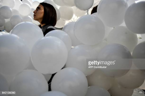 A woman holds white balloons as she takes part in a rally on September 3 in Moscow to commemorate the 13th anniversary of the 2004 hostagetaking at...