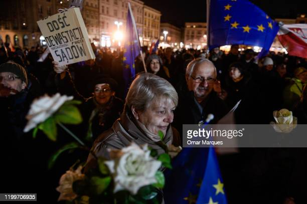 A woman holds white roses and an European Union flag during a protest against the recently signed judiciary law by the Polish President Andrezj Duda...