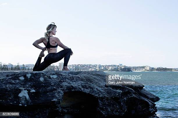 Woman holds yoga pose on a rock looking out to sea