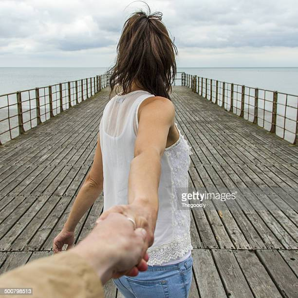 UK, Woman holing man's hand on pier