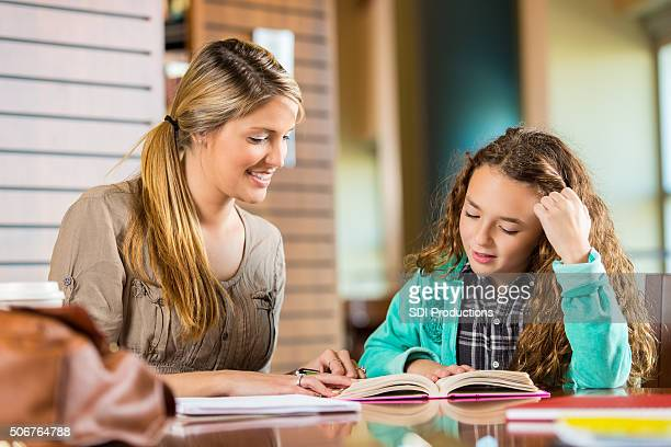 Woman homeschooling elementary age daughter in library