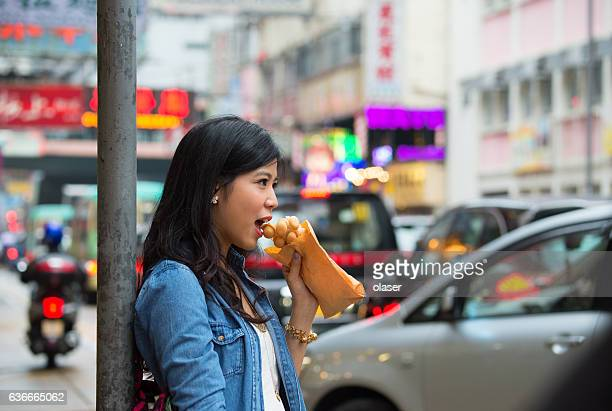 Woman Hong Kong street, standing eating traditional fast food, signs