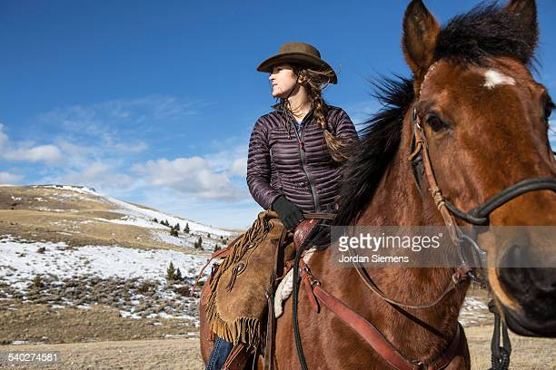 A woman horse back riding.