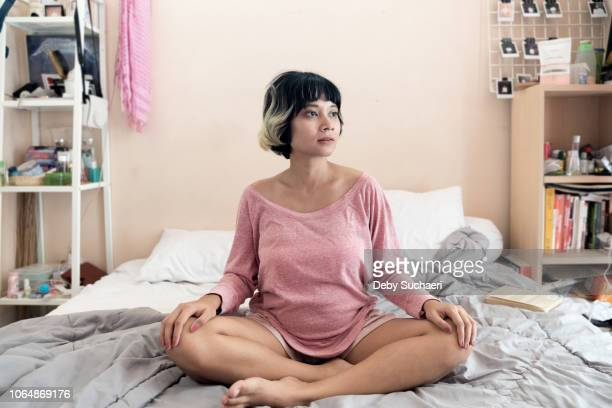 pregnant brown skin asian woman with short highlighted hair sitting on the bed at room smiling positively