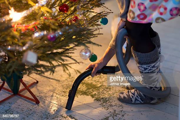 woman hovering needles under christmas tree - low section stock pictures, royalty-free photos & images