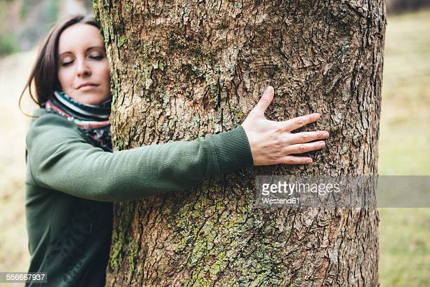 woman hugging a big tree trunk - tree hugging stock pictures, royalty-free photos & images