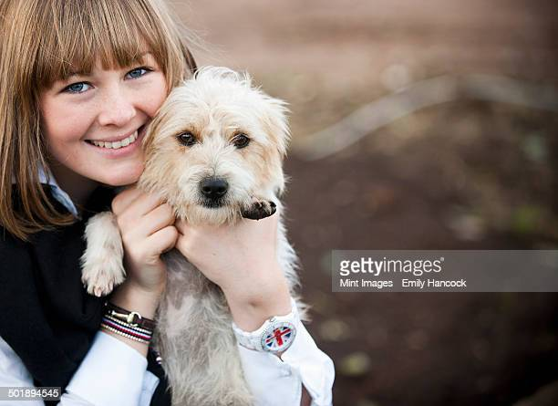 A woman hugging a small hairy terrier puppy.