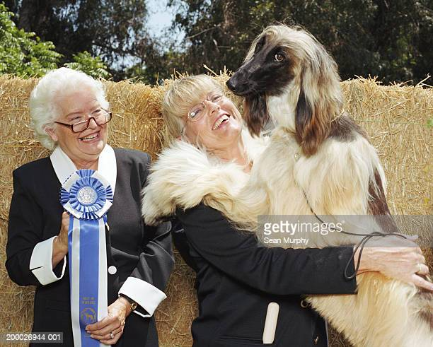 Woman hugging Afghan hound at dog show, female judge holding ribbon