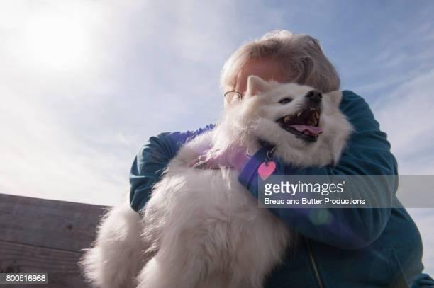 Woman Hugging American Eskimo Dog Outdoors