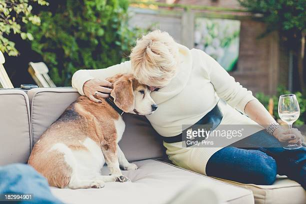 Woman hugging beagle dog on couch in the garden